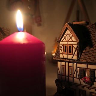 Rote Kerze vor zwei Keramik Lichthäusern