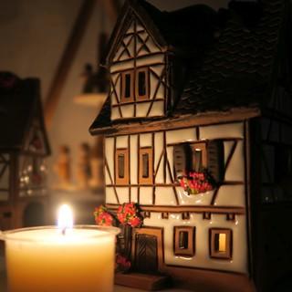 Weißes Fackwerk Keramik Lichthaus vor Kerze